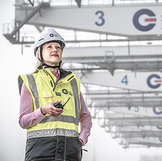 GCT employee standing in front of cranes